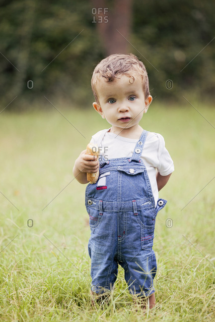 Portrait of little boy wearing denim dungarees standing on a meadow