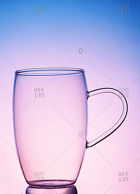 Glass cup against pink and blue light