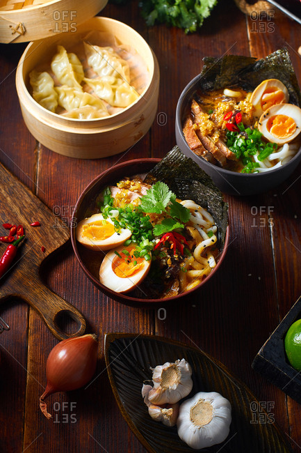 Asian cuisine dishes: pork ramen with soy-marinated eggs and gyoza dumplings served in a bamboo steamer on wooden background