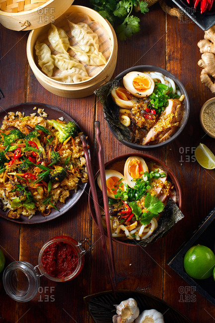Asian cuisine dishes: pork ramen with soy-marinated eggs, vegetarian fried rice and gyoza dumplings served in a bamboo steamer
