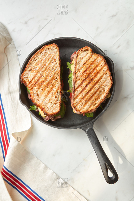 Freshly homemade two grilled sandwiches on a pan and marble grey background with copy space. Top view.