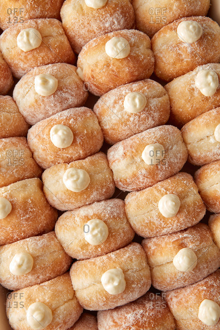 Freshly baked delicious homemade doughnuts with milk cream as a background. Top view.