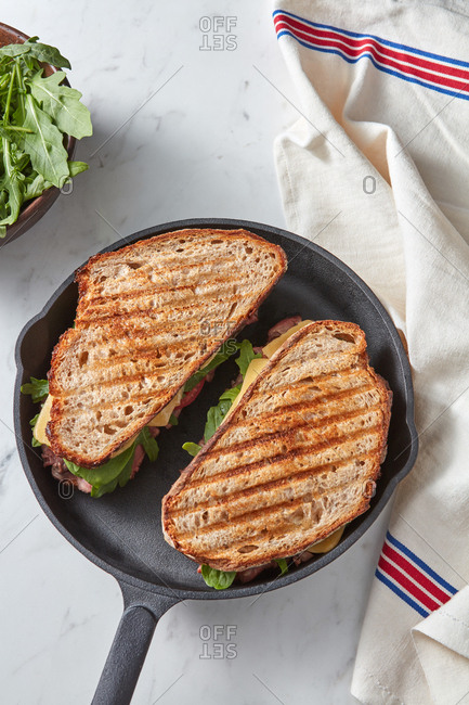 Black cast-iron pan with two freshly grilled homemade sandwiches from ham, cheese and vegetables on a light grey marble background with textile towel, copy space.