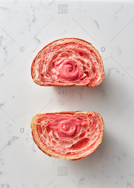 Two halves of homemade cut freshly baked croissant with fruits jam on a light grey marble background, place for text. Top view.