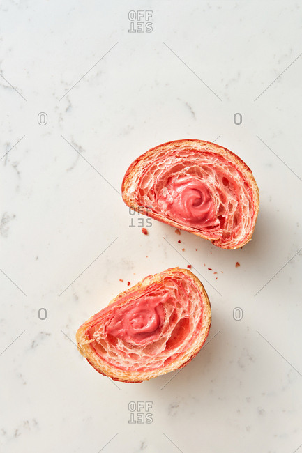Homemade cut croissant with berries jam on a light grey marble background, copy space. Top view.