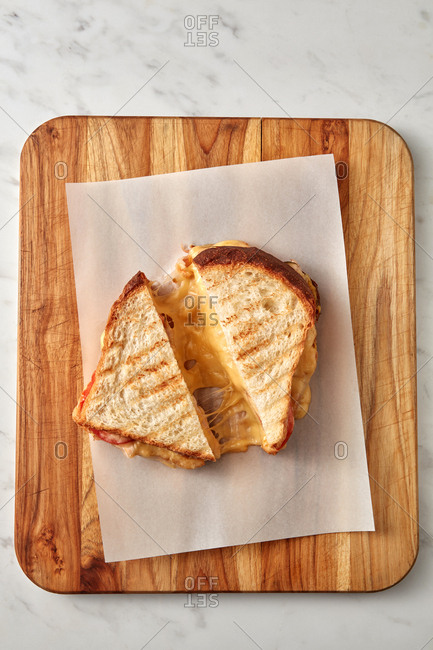 Homemade delicious freshly cooked sandwich on a wooden board on a marble gray background, copy space. Breakfast concept.