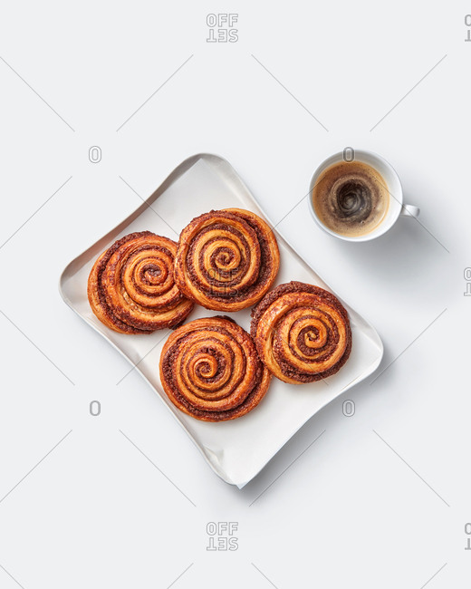 Homemade freshly baked cinnamon buns on a plate with cup of coffee on a light grey background, copy space. Sweet homemade pastry christmas baking.