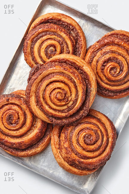 Top view of freshly baked homemade sweet cinnamon buns with spices on a baking sheet on a light grey background, copy space. Top view.