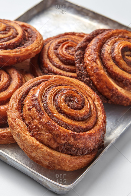 Freshly baked cinnamon buns with spices on the metal sheet. Sweet homemade pastry christmas baking. Close-up.