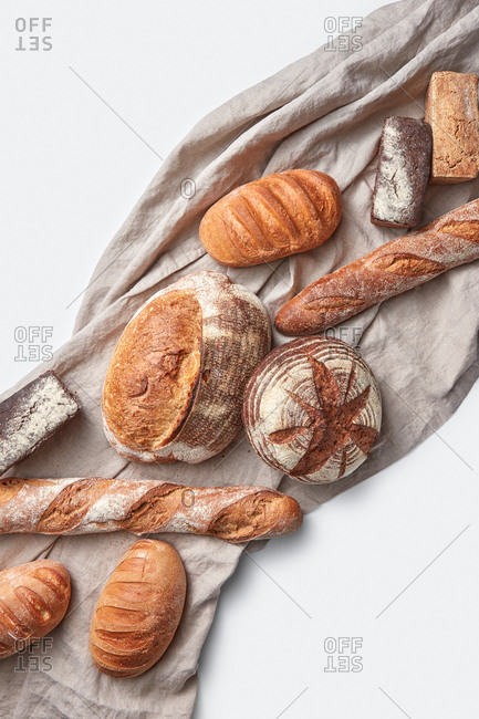 Textile towel with collection of freshly baked homemade organic bread on a light grey background, copy space. Top view.