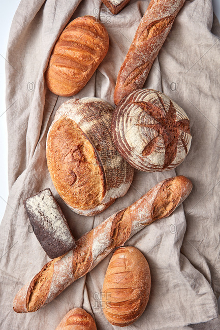 Assortment of natural homemade freshly baked bread on a grey textile towel with copy space. Top view.