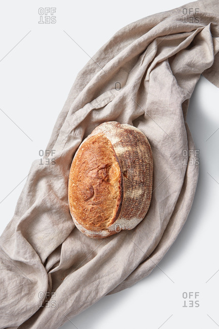 Loaf of natural organic homemade bread on a gray textile towel on a light background with copy space. Top view.