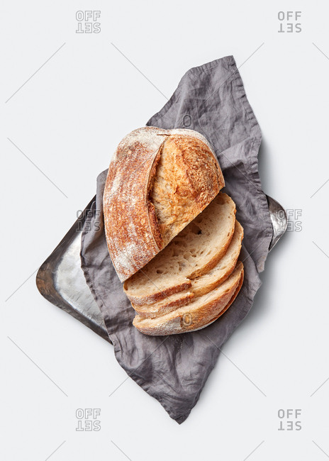 Slices of freshly baked natural organic wholegrain bread on a baking sheet with textile towel on a light grey background, copy space. Top view.