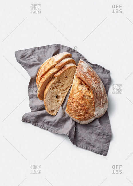Textile towel with slices of freshly baked homemade natural wholegrain loaf of bread on a light grey background with copy space. Top view.