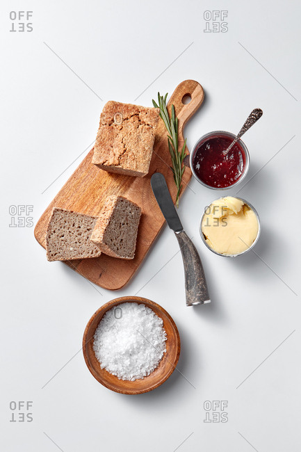 Healthy breakfast with homemade freshly baked bread, berries jam, butter and salt on a wooden board and light grey background with copy space. Top view.
