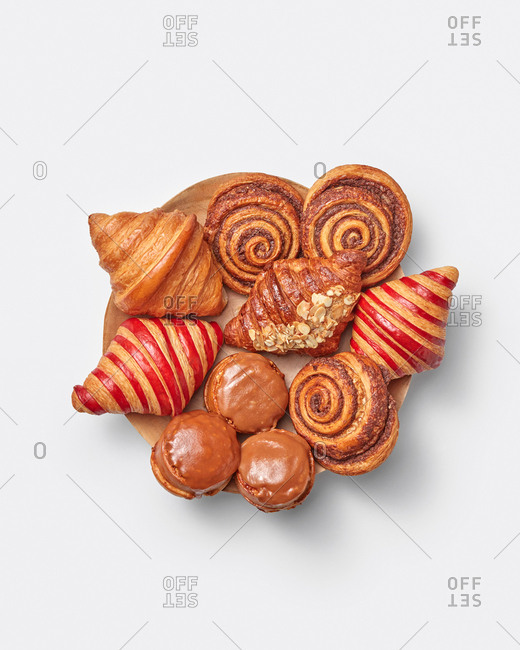 Homemade freshly baked sweet delicious pastry of croissants, doughnuts and cinnamon roll buns on a plate on a light grey background with copy space. Top view.