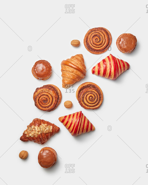 Delicious homemade sweet bakery dessert from freshly baked cinnamon roll buns, different croissants and caramel glazed doughnuts on a light grey background with copy space. Top view.