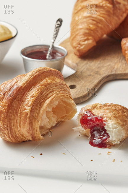 Freshly baked homemade crusty croissant with berries jam on a wooden board on a light grey background, copy space. Concept of continental breakfast.