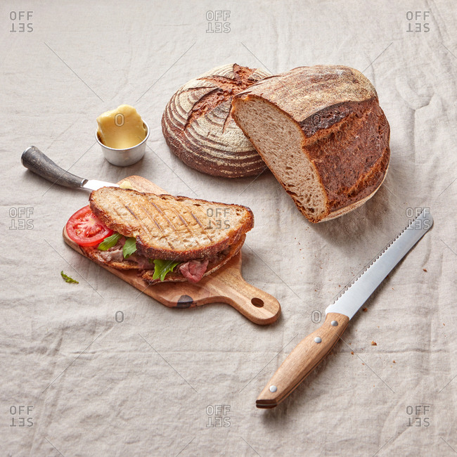 Freshly baked homemade wholegrain bread and homemade healthy sandwich with tomatoes and ham on a wooden board and textile background, copy space.