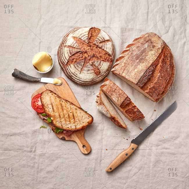 Homemade grilled sandwich with ham, vegetables and crusty bread on a wooden board and textile background, copy space. Top view.
