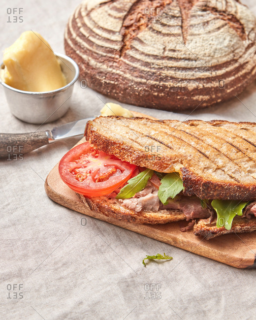 Delicious homemade sandwich with ham and fresh tomatoes and arugula on a wooden board on a textile background, copy space.