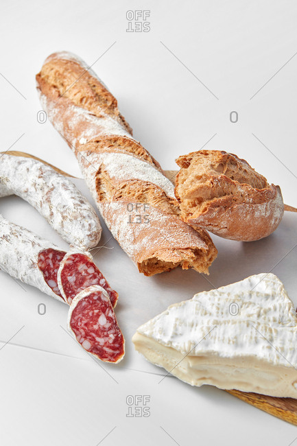Food set from homemade french wholegrain baguette, sausage and cheese on a light grey background with copy space.