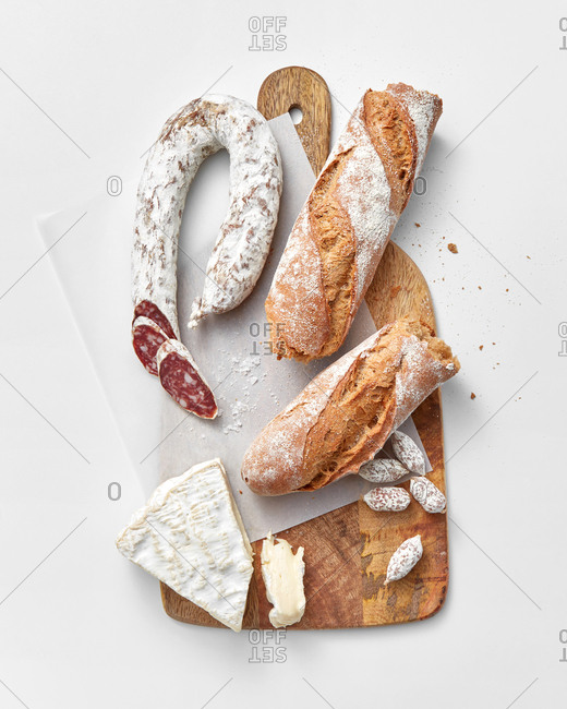 Italian food ingredients - freshly baked homemade bread, soft cheese and delicious sausage on a wooden board on a light grey background with copy space.