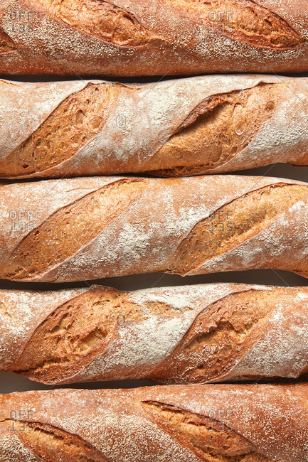 Freshly baked homemade organic baguettes as a background. Close up view.