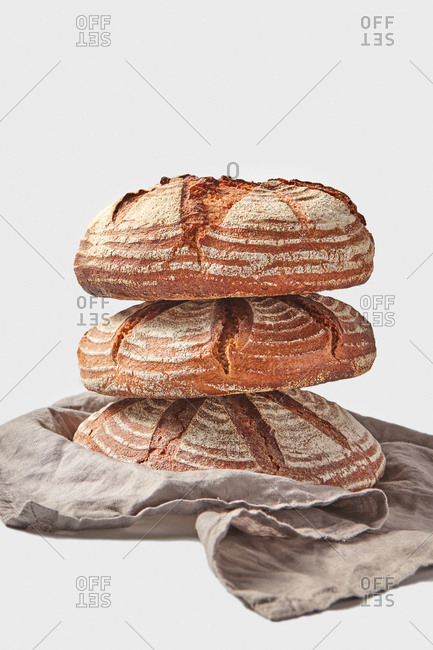 Stack of three freshly baked homemade wholegrain natural bread on a light grey background served textile towel with copy space.
