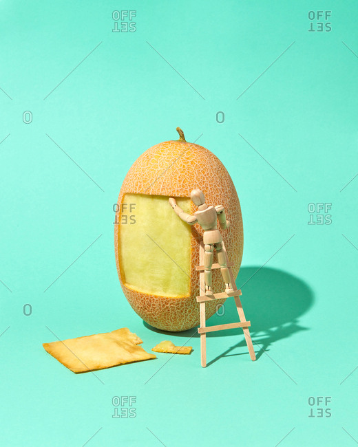 Square part of melon's peel is cut out by miniature articulation mannequin on a wooden ladder with hard shadows on a biscay green background, place for text.