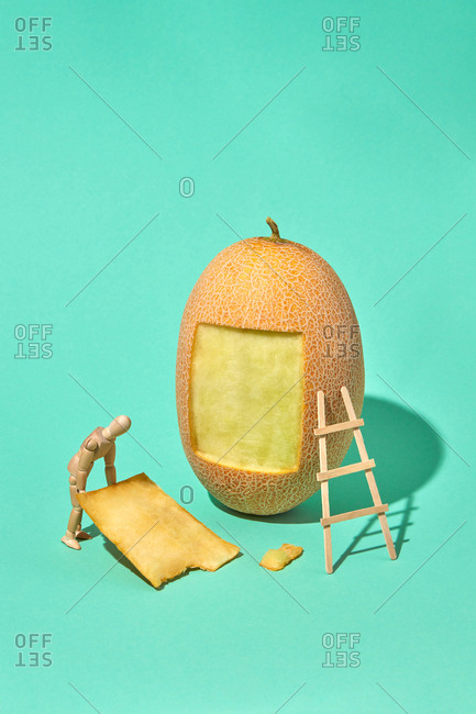 Strong wooden mannequin model holds square part of fresh ripe melon on a green biscay background with hard shadows, copy space.