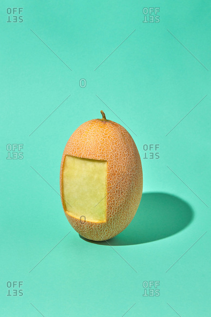 Square part of natural organic melon's peel is cut from fresh ripe fruit on a green biscay background with hard shadows, copy space.