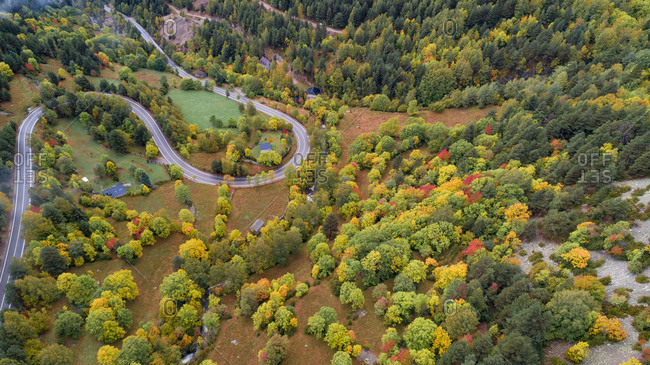 Winding road leading through colorful countryside in autumn