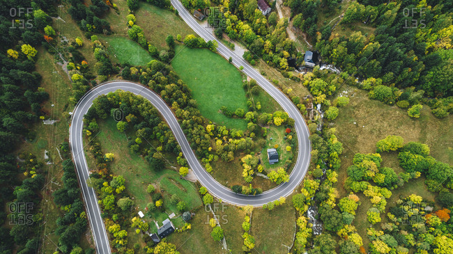 Bird's eye view over road leading through countryside in autumn