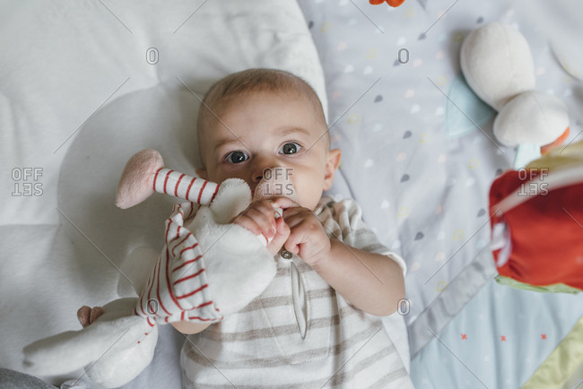Baby boy lays on floor with plush toy in mouth