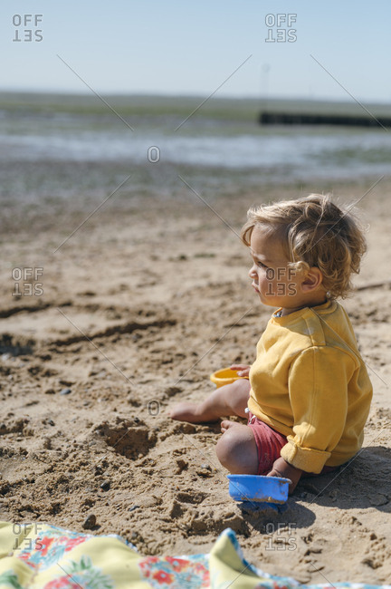 Boy plays in sand looking out to the sea