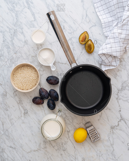 Overhead view of skillet and ingredients on white marble surface