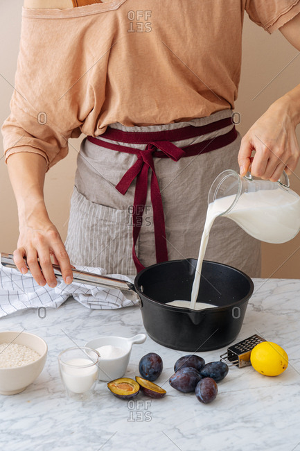 Woman pouring milk into large skillet surrounded by ingredients on white marble surface