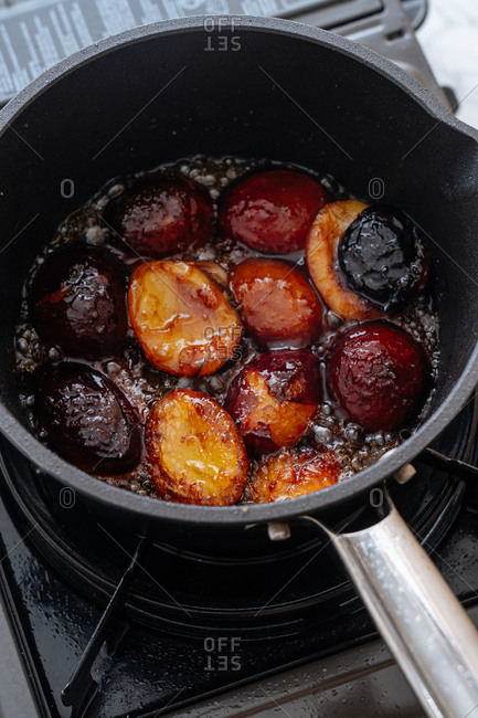 Overhead view of skillet cooking plums