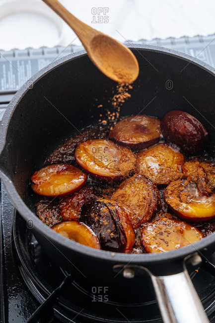 Seasons being added into a skillet cooking plums