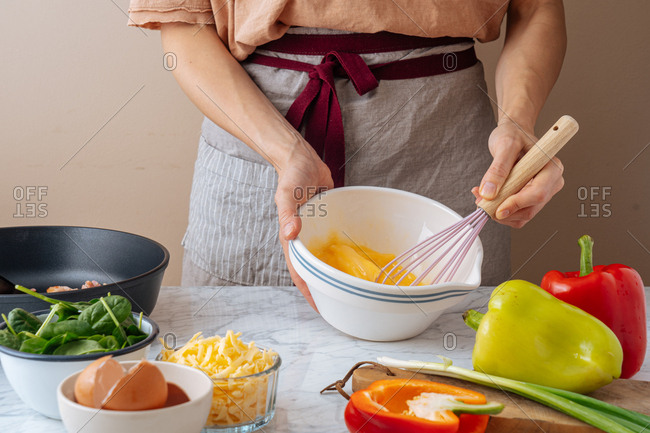 Chef whisking eggs in a bowl on white marble counter