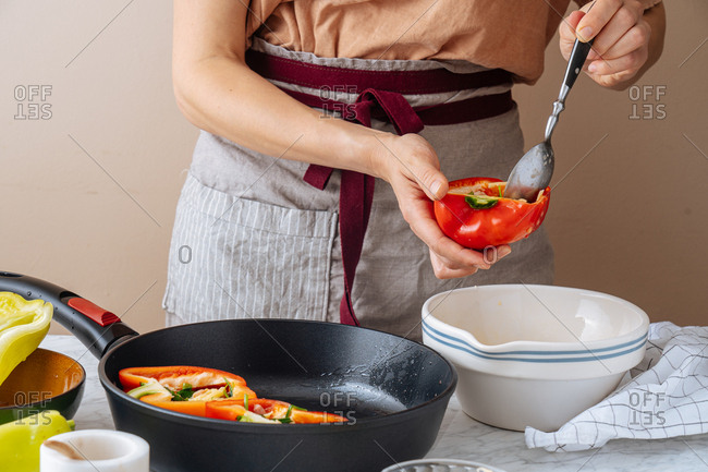 Woman adding egg mixture into bell pepper before placing it in a skillet