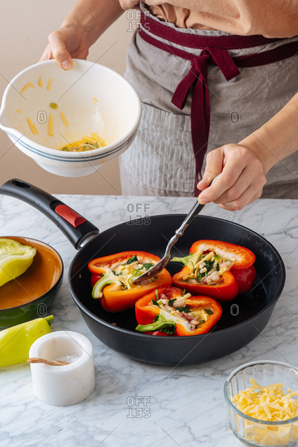 Woman adding egg mixture into bell peppers in a skillet
