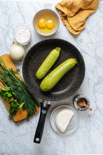 Overhead view of skillet with zucchinis and ingredients on white marble surface