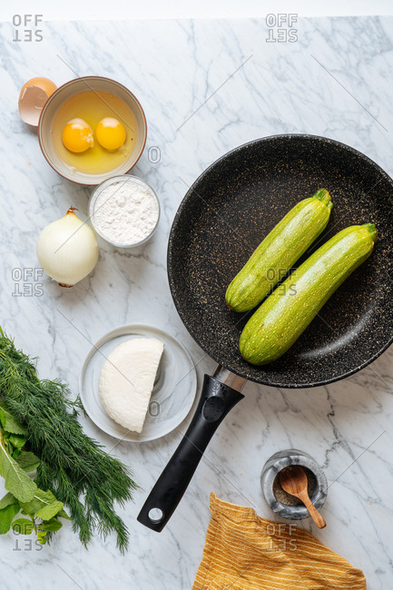 Top view of skillet with zucchinis and ingredients on white marble surface