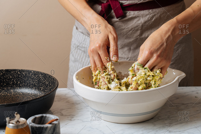 Woman mixing ingredients for zucchini fritters together in a bowl by hand
