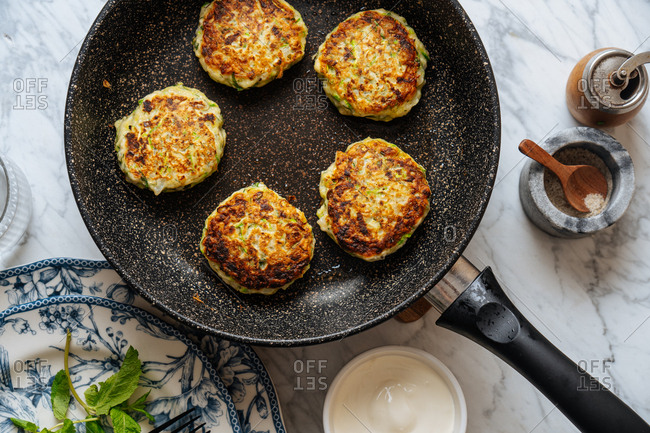 Overhead view of zucchini fritters in a frying pan