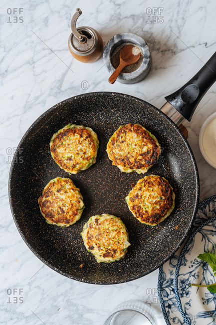 Top view of zucchini fritters in a frying pan