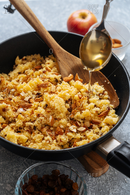 Honey being drizzled over a skillet with millet and almonds