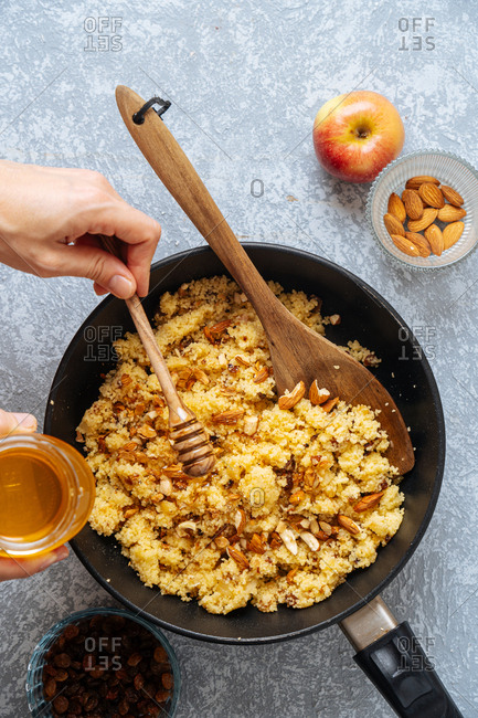 Woman drizzling honey over a skillet with millet and almonds